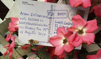 "In this Aug. 5, 2015 photo provided by Lucas Constanti, a postcard he received from Ukraine, which was sent as part of the ""Welcome to Donetsk"" postcard project, is displayed in Somerville, Mass. In hopes of putting a human face on war, Taylor-Lind and Alisa Sopova have been mailing such cards from eastern Ukraine to random people around the globe, informing the recipients that someone they had never met died in armed conflict there. (Lucas Constanti via AP)"