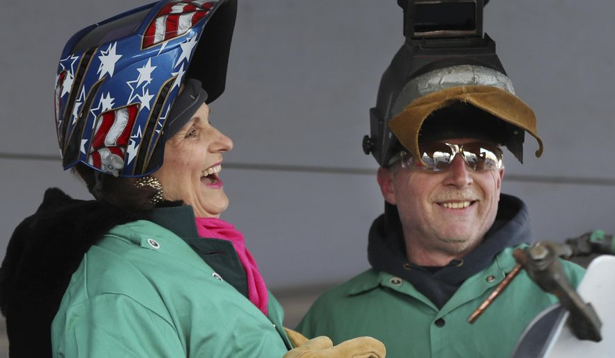 Lynda Johnson Robb, a daughter of the late President Lyndon B. Johnson, laughs after lifting her welding mask after assisting Bath Iron Works welder Timothy Trask at a keel-laying ceremony for the future USS Lyndon B. Johnson, Monday, Jan. 30, 2017, at Bath Iron Works in Bath, Maine. The ceremony marked the joining of two massive hull units, the first of several that will comprise the 610-foot Zumwalt class destroyer.(AP Photo/Robert F. Bukaty)