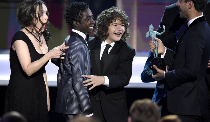 """Riz Ahmed, from right, presents the award for outstanding performance by an ensemble in a drama series for """"Stranger Things"""" to Gaten Matarazzo, Caleb McLaughlin, and Winona Ryder at the 23rd annual Screen Actors Guild Awards at the Shrine Auditorium & Expo Hall on Sunday, Jan. 29, 2017, in Los Angeles. (Photo by Chris Pizzello/Invision/AP)"""