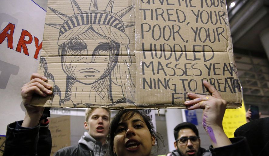 Demonstrators converge outside Terminal 5 of O'Hare International Airport, Sunday, Jan. 29, 2017, in Chicago, as people protest President Donald Trump's executive order banning travel to the United States by citizens of several countries. (AP Photo/Nam Y. Huh)
