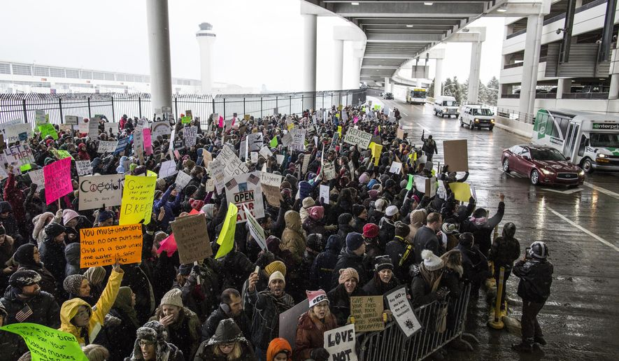 Demonstrators gather during a protest against President Donald Trump's executive order banning travel to the United States by citizens of several countries Sunday, Jan. 29, 2017, at Detroit Metropolitan Airport. (Jeffrey M. Smith/The Times Herald via AP)