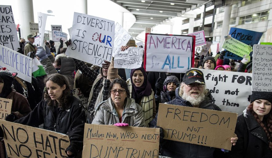 Demonstrators hold signs and chant during a protest against President Donald Trump's executive order banning travel to the United States by citizens of several countries Sunday, Jan. 29, 2017, at Detroit Metropolitan Airport. (Jeffrey M. Smith/The Times Herald via AP)