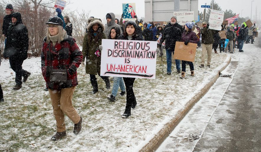 People march during a protest against an executive order on immigration from President Trump at Gerald R. Ford International Airport in Grand Rapids on Sunday, Jan. 29, 2017. Hundreds of people gathered to voice their opposition to President Trump's recent executive order barring citizens of several majority Muslim countries from entering the U.S. for 90 days. (Neil Blake/The Grand Rapids Press via AP)