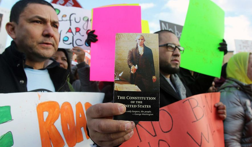 In this Jan. 29, 2017, rally participants Zorzy Borga, left, and Carlos Castaneda, holding a pamphlet of the US Constitution, both of Elizabeth, N.J., participate in a rally in Elizabeth outside the Homeland Security Detention Center protesting President Donald Trump's executive order banning travel to the U.S. by citizens of Iraq, Syria, Iran, Sudan, Libya, Somalia or Yemen. (Thomas E. Franklin/The Record via AP)