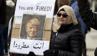 A woman carries a sign outside of the White House during a demonstration to denounce President Donald Trump's executive order that bars citizens of seven predominantly Muslim-majority countries from entering the United States on Sunday, Jan. 29, 2017, in Washington.(AP Photo/Jose Luis Magana)