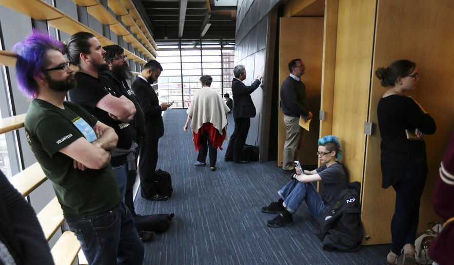 "Attendees overflow into a hallway outside a Seattle City Council meeting Monday, Jan. 30, 2017, in Seattle. Council members passed a resolution Monday reaffirming that Seattle is a ""welcoming city"" that treats residents equally regardless of their refugee or immigration status. (AP Photo/Ted S. Warren)"