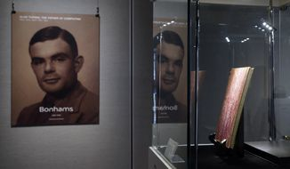 """In this Thursday, March 19, 2015, file photo, a notebook of British mathematician Alan Turing is displayed in front of his portrait during an auction preview in Hong Kong. Thousands of men convicted under now-abolished anti-homosexuality laws in Britain have been pardoned posthumously under a law passed on Tuesday, Jan. 31, 2017, and many more still alive can now apply to have their criminal convictions wiped out. Calls for a general pardon have noted the 1954 suicide of World War II codebreaking hero Alan Turing after his conviction for """"gross indecency."""" After he received a posthumous royal pardon in 2013, pressure for pardons intensified. (AP Photo/Kin Cheung, file)"""