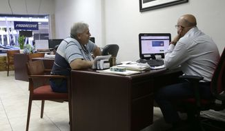 "Sami Jamaleddine, left, signs up for health insurance offered under the Affordable Care Act with insurance agent Michael Khoury, right, Tuesday, Jan. 31, 2017, in Miami. The enrollment period for the federal health care law known as ""Obamacare"" ends at the end of the day Tuesday. The Republican-lead Senate has passed a measure to take the first step forward on dismantling President Barack Obama's health care law. (AP Photo/Lynne Sladky)"