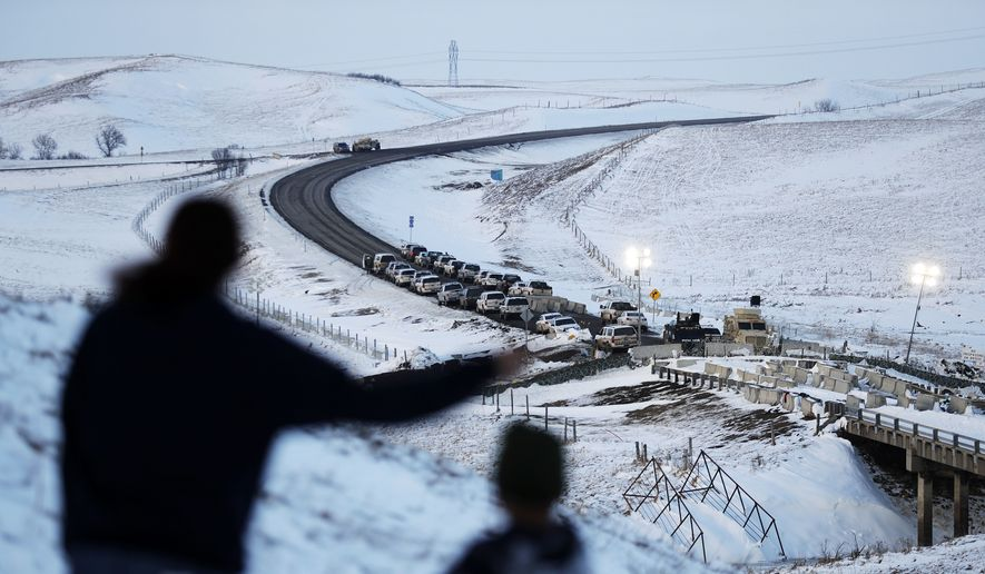 In this Dec. 3, 2016, file photo, law enforcement vehicles line a road leading to a blocked bridge next to the Oceti Sakowin camp where people have gathered to protest the Dakota Access oil pipeline in Cannon Ball, N.D. North Dakota Sen. John Hoeven said Tuesday, Jan. 31, 2017, that the Acting Secretary of the Army has directed the Army Corps of Engineers to proceed with an easement necessary to complete the Dakota Access pipeline. (AP Photo/David Goldman, File)