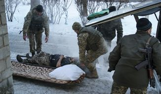 A wounded Ukrainian soldier is treated in Avdiivka, Ukraine, Tuesday, Jan. 31, 2017. Fighting between government troops and Russia-backed separatist rebels in eastern Ukraine escalated on Tuesday, killing at least eight people late Monday and early Tuesday, injuring dozens and briefly trapping more than 200 coal miners underground, the warring sides reported.(AP Photo/Inna Varenytsia)