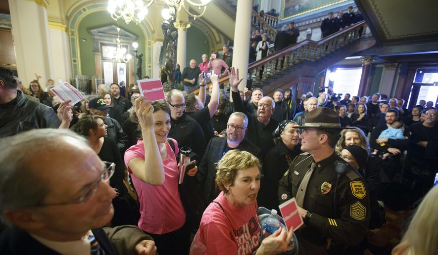 Planned Parenthood supporters dressed in pink head to a meeting as opponents dressed in black as they sing before a Senate committee meeting on a bill that would defund Planned Parenthood, Tuesday, Jan. 31, 2017, in Des Moines, Iowa. (Zach Boyden-Holmes/The Des Moines Register via AP)