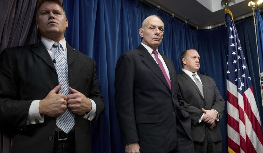 Homeland Security Secretary John Kelly, center, accompanied by U.S. Immigration and Customs Enforcement Acting Director Thomas Homan, right, and a member of his security detail, attends a news conference at the U.S. Customs and Border Protection headquarters in Washington, Tuesday, Jan. 31, 2017, to discuss the operational implementation of the president's executive orders. (AP Photo/Andrew Harnik)