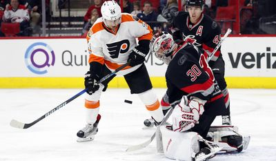 Carolina Hurricanes goalie Cam Ward (30) blocks the shot of Philadelphia Flyers' Matt Read (24) with Hurricanes' Victor Rask (49) nearby during the first period of an NHL hockey game, Tuesday, Jan. 31, 2017, in Raleigh, N.C. (AP Photo/Karl B DeBlaker)