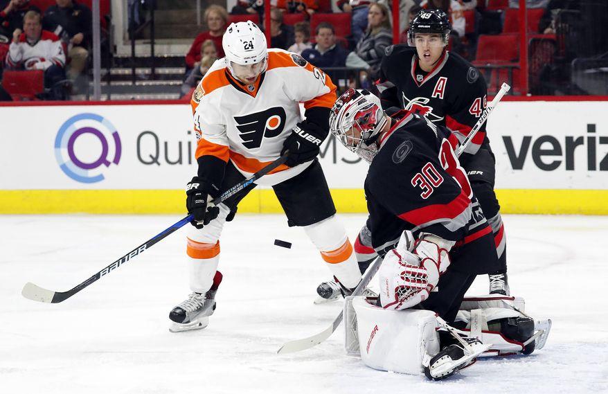 Carolina Hurricanes goalie Cam Ward (30) blocks the shot of Philadelphia Flyers' Matt Read (24) with Hurricanes' Victor Rask (49) nearby during the first period of an NHL hockey game, Tuesday, Jan. 31, 2017, in Raleigh, N.C. (AP Photo/Karl B DeBlaker)