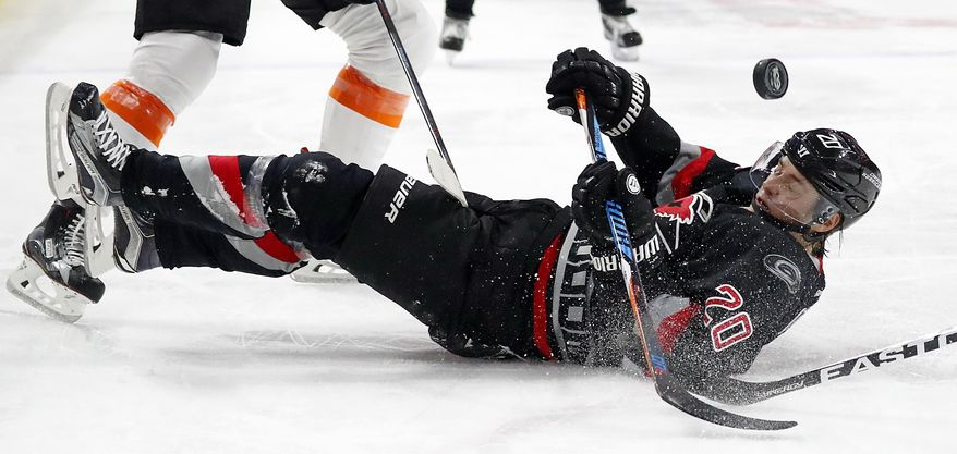 Carolina Hurricanes' Sebastian Aho (20) gets thrown to the ice by Philadelphia Flyers' Sean Couturier, during the second period of an NHL hockey game, Tuesday, Jan. 31, 2017, in Raleigh, N.C. (AP Photo/Karl B DeBlaker)