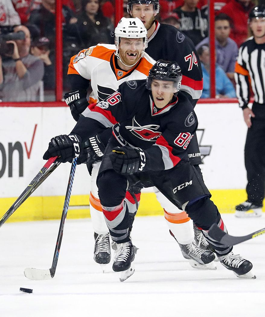 Carolina Hurricanes' Teuvo Teravainen (86) works the puck in front of Philadelphia Flyers' Sean Couturier (14) during the second period of an NHL hockey game, Tuesday, Jan. 31, 2017, in Raleigh, N.C. (AP Photo/Karl B DeBlaker)