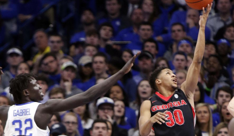 Georgia's J.J. Frazier (30) shoots near the defense of Kentucky's Wenyen Gabriel (32) during the first half of an NCAA college basketball game, Tuesday, Jan. 31, 2017, in Lexington, Ky. (AP Photo/James Crisp)