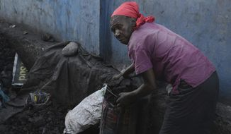 In this Wednesday, Jan. 25, 2017 photo, a woman gathers charcoal in a depot to sell at a local market, in Les Cayes, Haiti. A growing number of international researchers and Haitian agronomists are urging a major policy rethink of charcoal, arguing that regulated production of the long-maligned fuel can be sustainable and a driver of reforestation efforts. (AP Photo/David McFadden)