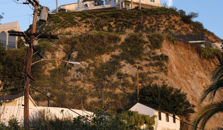 A broken utility poll remains standing, left, as a deck of a home, right, juts out precariously over an area where a landslide occurred in the Hollywood Hills area of Los Angeles on Tuesday, Jan. 31, 2017. City inspectors are at a Hollywood Hills home where the backyard crumbled, sending mud and debris down a slope, across a street and into the front yards of two other houses. A fire department spokesman says the Monday night slide took out power lines and buried one vehicle but did not reach the inside of the homes. No one was injured. (AP Photo/Richard Vogel)