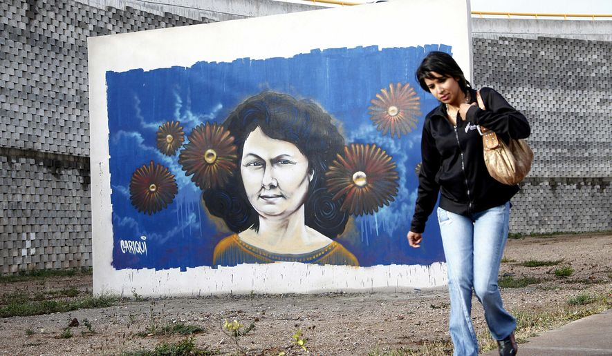 A woman walks past a mural of slain environmentalist and indigenous leader Berta Caceres in Tegucigalpa, Honduras, Tuesday, Jan. 31, 2017. Global Witness released a report linking top Honduran politicians and members of the business elite to violence against land activists. The international watchdog group says Honduras is the most dangerous country in the world for environmental defenders, with more than 120 of them killed there since 2010. That includes last year's murder of Caceres, who was awarded the prestigious Goldman Environmental Prize for her work leading protests in opposition to a hydroelectric project on her Lenca people's ancestral lands. (AP Photo/Fernando Antonio)