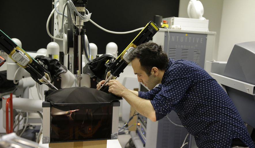 Iranian-born bioengineer researcher Nima Enayati works on a robotic surgery machine during an interview with the Associated Press at the Polytechnic University of Milan, Italy, Tuesday, Jan. 31, 2017. An Iranian researcher at Milan's Polytechnic University, Enayati was refused check-in Monday at Milan's Malpensa Airport for his U.S.-bound flight on Turkish Airlines after the Trump administration's executive order came down. (AP Photo/Luca Bruno)