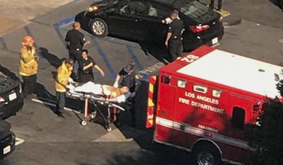 In this photo provided by Nick Walsh, paramedics place a man in an ambulance after a stabbing and police shooting at a Jack in the Box in Los Angeles' Hollywood district Tuesday, Jan. 31, 2017. Police say officers were answering a report of the stabbing Tuesday when they saw someone stabbing people inside the restaurant. (Nick Lewis via AP)