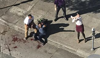 In this photo provided by Nick Walsh, passersby come to the aid of a bloodied man after a stabbing and police shooting at a Jack in the Box in Los Angeles' Hollywood district Tuesday, Jan. 31, 2017. Police say officers were answering a report of the stabbing Tuesday when they saw someone stabbing people inside the restaurant. (Nick Lewis via AP)