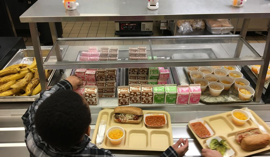 FILE - In this Jan. 25, 2017, file photo, students fill their lunch trays at J.F.K Elementary School in Kingston, N.Y., where all meals are now free under the federal Community Eligibility Provision. A donor inspired by a tweet raised money to pay off lunch debt in districts around the country, as well as thousands of dollars in overdue lunch fees at other schools in the Kingston district. (AP Photo/Mary Esch, File)