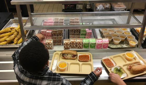 In this Jan. 25, 2017, file photo, students fill their lunch trays at J.F.K Elementary School in Kingston, N.Y., where all meals are now free under the federal Community Eligibility Provision. A donor inspired by a tweet raised money to pay off lunch debt in districts around the country, as well as thousands of dollars in overdue lunch fees at other schools in the Kingston district. (AP Photo/Mary Esch, File) **FILE**