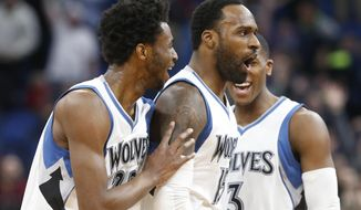 Minnesota Timberwolves' Shabazz Muhammad, center, is congratulated by Andrew Wiggins, left, and Kris Dunn after sinking a half-court shot at the buzzer ending the third quarter during an NBA basketball game against the Orlando Magic, Monday, Jan. 30, 2017, in Minneapolis. The Timberwolves won 111-105 in overtime. (AP Photo/Jim Mone)