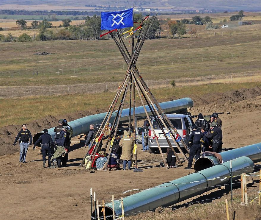 FILE- In this Oct. 10, 2016, file photo, Law enforcement officers, left, drag a person from a protest against the Dakota Access Pipeline, near the town of St. Anthony in rural Morton County, N.D. North Dakota Sen. John Hoeven said Tuesday, Jan. 31, 2017, that the Acting Secretary of the Army has directed the Army Corps of Engineers to proceed with an easement necessary to complete the Dakota Access pipeline. (Tom Stromme/The Bismarck Tribune via AP, File)