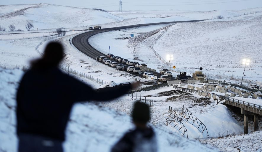 FILE- In this Dec. 3, 2016, file photo, law enforcement vehicles line a road leading to a blocked bridge next to the Oceti Sakowin camp where people have gathered to protest the Dakota Access oil pipeline in Cannon Ball, N.D. North Dakota Sen. John Hoeven said Tuesday, Jan. 31, 2017, that the Acting Secretary of the Army has directed the Army Corps of Engineers to proceed with an easement necessary to complete the Dakota Access pipeline. (AP Photo/David Goldman, File)