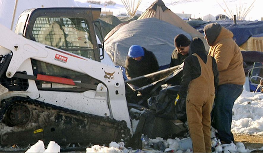 This Monday, Jan. 30, 2017, photo from video provided by KXMB in Bismarck, N.D., shows cleanup beginning at a North Dakota encampment near Cannon Ball where Dakota Access oil pipeline opponents have protested for months. The Standing Rock Sioux has organized the cleanup with the help of the Thunder Valley Community Development Corp. from South Dakota's Pine Ridge Reservation, which has arranged for heavy equipment including front-end loaders, dump trucks and skid-steer loaders. The work could take weeks, and the cost isn't known. (KXMB via AP)