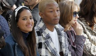 FILE - In this March 8, 2016, file photo, from left, Helen Lasichanh, her husband, Pharrell Williams, and French actress Isabelle Huppert attend the Chanel's Fall-winter 2016-2017 ready to wear collection presented in Paris. Williams' publicist said on Jan. 31, 2017, that he and Lasichanh have welcomed triplets. (AP Photo/Francois Mori, File)