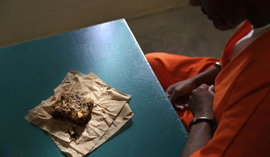In this Oct. 26, 2016 photo, a nutraloaf, a meal typically given to inmates for misbehavior involving food or bodily waste, sits in front of inmate Kevin Dickens during an interview with The Associated Press at James T. Vaughn Correctional Center in Smyrna, Del. Dickens holds the dubious distinction of being on a loaf diet for longer than any other Delaware inmate -- five consecutive weeks in 2009. Originally sentenced to four years behind bars in 2002 for assault, has been convicted 18 times since then for assault in a detention facility. Without those additional 18 charges, he would have been released in 2006, but he is now looking at a release date of 2051. (AP Photo/Patrick Semansky)