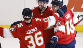 Florida Panthers defenseman Jason Demers, center, celebrates with left wing Jussi Jokinen (36) and right wing Reilly Smith (18) after Demers scored a goal during the third period of the team's NHL hockey game against the Ottawa Senators, Tuesday, Jan. 31, 2017, in Sunrise, Fla. The Panthers defeated the Senators 6-5. (AP Photo/Wilfredo Lee)