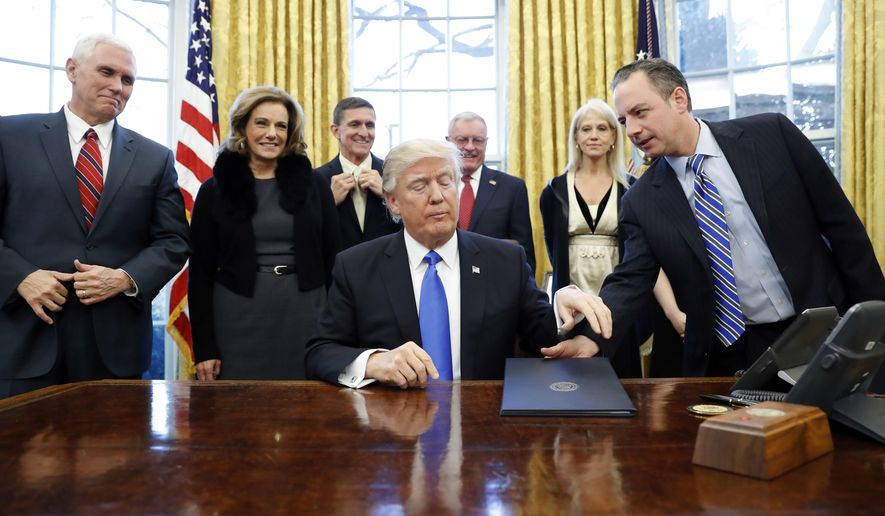 President Donald Trump is handed an Executive Order to sign by White House Chief of Staff Reince Priebus, right, with Vice President Mike Pence, left, and others nearby, in the Oval Office of the White House, Saturday, Jan. 28, 2017 in Washington. (AP Photo/Alex Brandon)