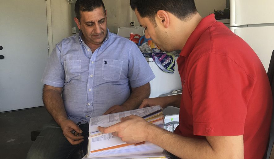 Iraqi refugee Raed Rabban, left, meets with Mark Arabo, president of the Minority Humanitarian Foundation, which helps Iraqi Christians settle in the United States, in his garage in El Cajon, Calif., Monday, Jan. 30, 2017. Rabban's younger brother, Luey, who works as cook in a Baghdad restaurant, received refugee status in the United States about eight months ago. Luey was waiting for his turn to emigrate but said Monday by phone he is unsure now if that day will ever come. (AP Photo/Eliott Spagat)