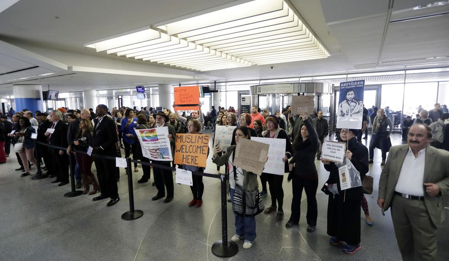 Protesters hold signs at San Francisco International Airport to denounce President Donald Trump's executive order that bars citizens of seven predominantly Muslim-majority countries from entering the U.S., Monday, Jan. 30, 2017, in San Francisco. (AP Photo/Marcio Jose Sanchez)