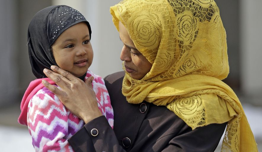 Somali refugee Nimo Hashi holds her daughter Taslim at their home Tuesday, Jan. 31, 2017, in Salt Lake City. Hashi bought a new kitchen table and couches for her Salt Lake City apartment in joyful anticipation of reuniting Friday with her husband for the first time in nearly three years. But he won't be arriving as planned to see her and the 2-year-old daughter he's never met. He is among hundreds of people stuck in limbo after President Donald Trump's executive order temporarily banned refugees and nearly all travelers from seven Muslim-majority countries, including Somalia. (AP Photo/Rick Bowmer)