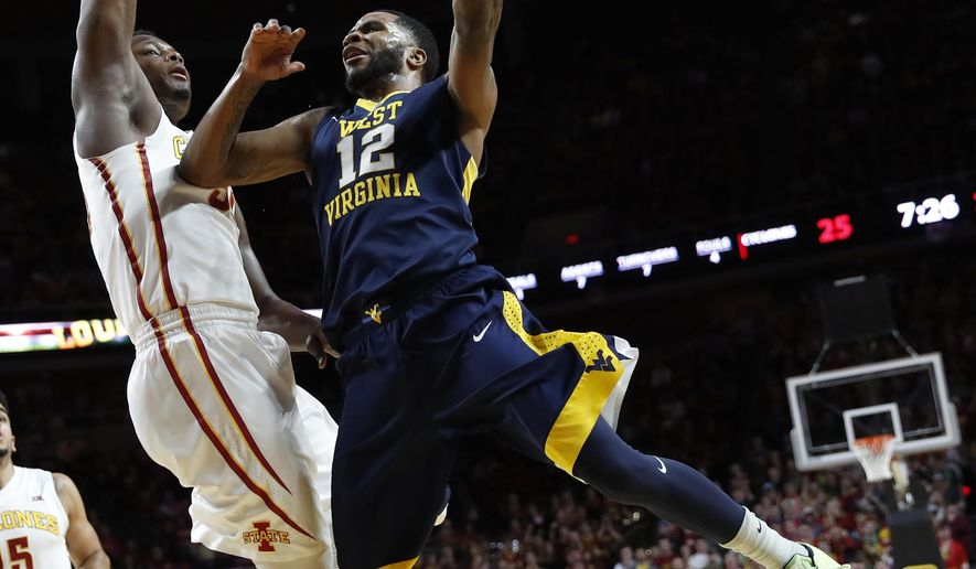 West Virginia guard Tarik Phillip (12) drives to the basket past Iowa State guard Deonte Burton during the first half of an NCAA college basketball game, Tuesday, Jan. 31, 2017, in Ames, Iowa. (AP Photo/Charlie Neibergall)