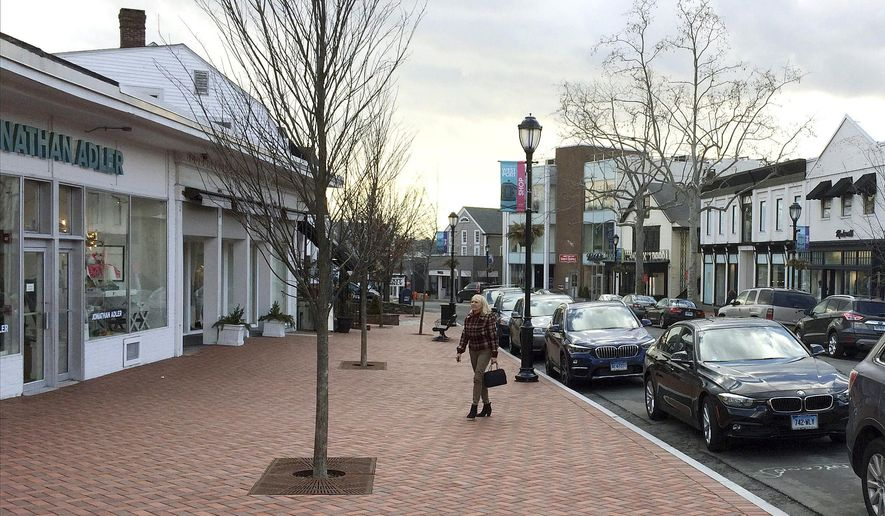 In this Thursday, Jan. 26, 2017 photo, a woman walks near shops in downtown Westport, Conn. A town-sponsored essay contest on the topic of white privilege has stirred controversy in the affluent, overwhelmingly white town on Connecticut's shoreline. (AP Photo/Michael Melia)