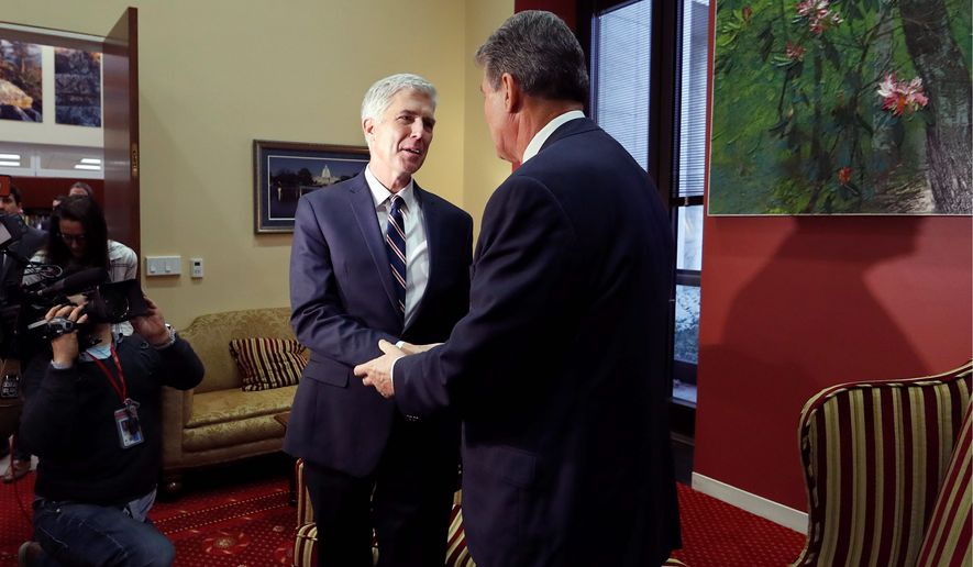 Supreme Court nominee Neil Gorsuch (left) met on Wednesday with Sen. Joe Manchin III, West Virginia Democrat, and others who will decide his fate. (Associated Press)