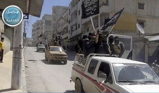 FILE - In this file photo posted on the Twitter page of Syria's al-Qaida-linked Nusra Front on April 25, 2015, which is consistent with AP reporting, Nusra Front fighters stand on their vehicles and wave their group's flags as they tour the streets of Jisr al-Shughour, Idlib province, Syria. The battle for Aleppo has gripped the world, but it is hardly the only active front across Syria. One of the next targets for the forces of Bashar Assad will probably be the heartland of rebel territory, the neighboring Idlib province. (Al-Nusra Front Twitter page via AP, File)