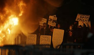 Protestors watch a fire on Sproul Plaza during a rally against the scheduled speaking appearance by Breitbart News editor Milo Yiannopoulos on the University of California at Berkeley campus on Wednesday, Feb. 1, 2017, in Berkeley, Calif. The event was cancelled due to size of the crowd and several fires being set. (AP Photo/Ben Margot)