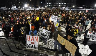 A crowd gathers on the State House lawn in Montpelier, Vt., Wednesday, Feb. 1, 2017, for a solidarity candlelight vigil in response to President Donald Trump's recent travel ban on refugees and citizens of certain majority-Muslim countries. (Jeb Wallace-Brodeur/The Times Argus via AP)