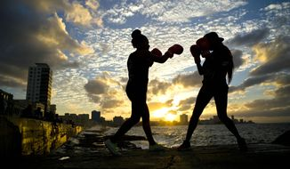 "In this Jan. 30, 2017 photo, boxers Idamerys Moreno, left, and Legnis Cala, train during a photo session on Havana's sea wall, in Cuba. Moreno and Cala are part of a group of up-and-coming female boxers on the island who want government support to form Cuba's first female boxing team and help dispel a decades-old belief once summed up by a former top coach: ""Cuban women are meant to show the beauty of their face, not receive punches."" (AP Photo/Ramon Espinosa)"
