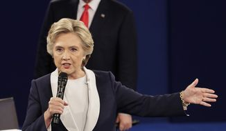 Republican presidential nominee Donald Trump listens to Democratic presidential nominee Hillary Clinton during the second presidential debate at Washington University in St. Louis on Oct. 9, 2016. (Associated Press) **FILE**