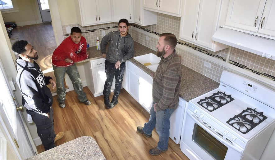 In a Wednesday, Jan. 25, 2017 photo, from left, Kevin Polite, Ryan Ocasio, Christian Maldonado and Eddie Patton gather in the kitchen of their next renovation project, a home in the 300 block of Laurel Street, in Lancaster, Pa. Polite, who was paroled from state prison in 2014, is part of a job-training program to give individuals with a criminal record a second chance at employment. Since November, Polite has been a Community Action Partnership employee in the nonprofit's new, four-man remodeling crew.   (Dan Marschka/LNP via AP)