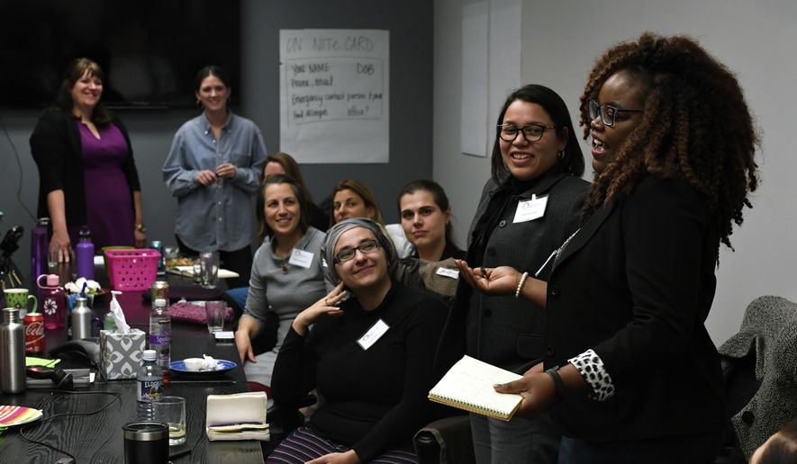 In this Jan. 25, 2017 photo, Shontel Lewis, right, introduces Vanessa Quintana, second from right, during an orientation meeting for Emerge Colorado on in Denver. Emerge is a national organization that recruits and trains Democratic women to run for local and state races - and then run again for a higher office. Emerge Executive director Jenny Willford stands at back left. (Helen H. Richardson/The Denver Post via AP)